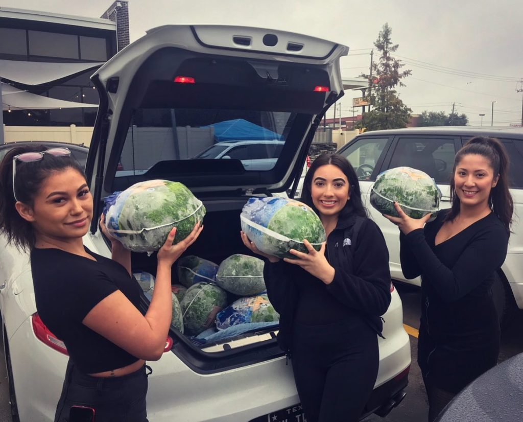 Prime Social employees show off frozen turkey donations for Full House Feast